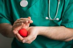 Docteur masculin dans le costume vert avec des prises de stéthoscope au coeur rouge lumineux de mains Horizontal, soins de santé, photos stock