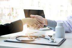 Docteur masculin dans le manteau blanc serrant la main au patient féminin après s Image libre de droits