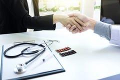 Docteur masculin dans le manteau blanc serrant la main au patient féminin après s Photos stock