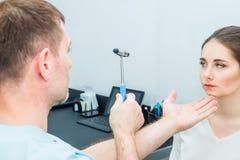 Docteur masculin de neurologue inspectant le jeune système nerveux patient femelle du ` s utilisant un marteau Examen physique ne Photo libre de droits