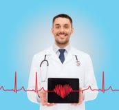 Docteur masculin de sourire avec le PC de comprimé Image stock