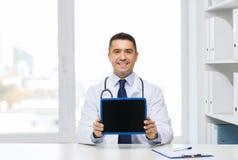 Docteur masculin de sourire montrant à PC de comprimé l'écran vide Photos stock