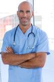 Docteur masculin de sourire regardant l'appareil-photo avec des bras croisés Image stock