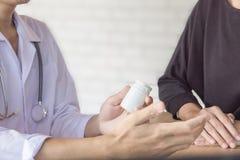 Docteur masculin donnant la bouteille de médecine au patient féminin dans un hôpital images stock
