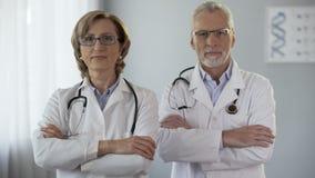 Docteur masculin et féminin regardant des bras de croisement d'appareil-photo, publicité, garantie clips vidéos