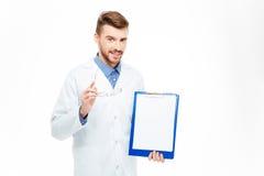 Docteur masculin heureux montrant le presse-papiers vide Image stock