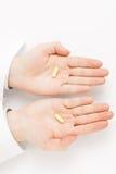 Docteur masculin holdling une pilule au-dessus de chacune de ses paumes - tir de studio images stock