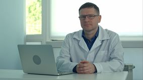 Docteur masculin mûr s'asseyant au bureau avec l'ordinateur portable et regardant l'appareil-photo dans son bureau de clinique Photo libre de droits