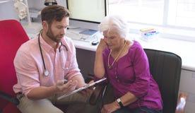 Docteur masculin montrant la prescription à la femme supérieure dans la chambre de clinique photos libres de droits