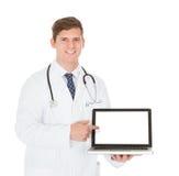 Docteur masculin montrant sur l'ordinateur portable Photos stock