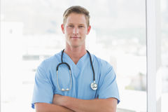 Docteur masculin sûr regardant l'appareil-photo avec des bras croisés photographie stock