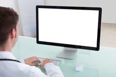 Docteur masculin sûr travaillant sur l'ordinateur au bureau Image stock
