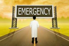 Docteur masculin se tenant sur la route et regardant avec le grand signe de l'EMER Photo libre de droits