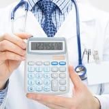 Docteur masculin tenant la calculatrice dans des mains - concept de soins de santé image libre de droits