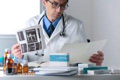 Docteur masculin travaillant à son bureau de bureau, représentant médical de examen Photographie stock