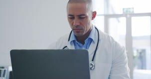 Docteur masculin utilisant l'ordinateur portable dans le bureau 4k banque de vidéos