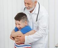 Docteur montrant des exercices au garçon sur la consultation photos libres de droits