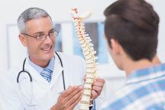 Docteur montrant l'épine anatomique à son patient Photographie stock libre de droits