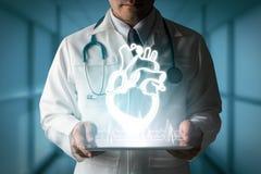 Docteur montrant l'hologramme de coeur à partir de l'ordinateur Photographie stock libre de droits