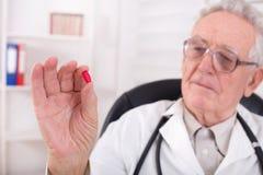 Docteur montrant le comprimé rouge photos libres de droits