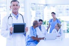 Docteur montrant le PC de comprimé au cours de la réunion Photographie stock