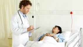 Docteur parlant au patient malade dans le lit banque de vidéos