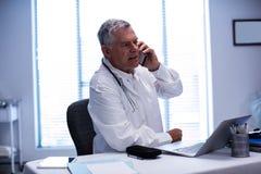 Docteur parlant au téléphone portable tout en à l'aide de l'ordinateur portable Photos stock
