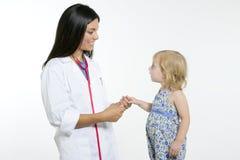 Docteur pédiatrique de Brunette avec la petite fille blonde Image stock