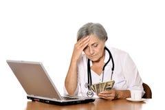 Docteur plus âgé avec des dollars Images stock