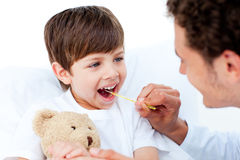 Docteur positif prenant la température de petit garçon Image libre de droits