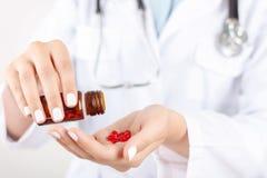 Docteur positif tenant des pilules Photos stock