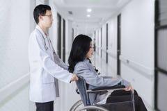 Docteur poussant le patient avec le fauteuil roulant dans l'hôpital images libres de droits