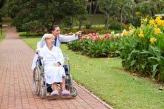 Docteur poussant le patient de fauteuil roulant en stationnement Photo libre de droits