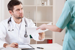 Docteur prenant des documents d'une infirmière photographie stock libre de droits