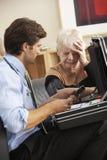 Docteur prenant la tension artérielle de la femme supérieure à la maison Image stock