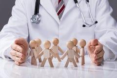 Docteur Protecting Wooden Figures image stock