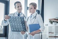 Docteur qualifié intéressé tenant et regardant son collègue Image stock