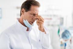 Docteur réfléchi dans le nez émouvant de masque protecteur photo libre de droits