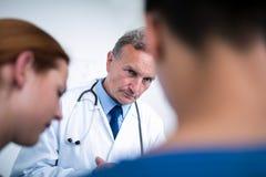 Docteur réfléchi se tenant avec des chirurgiens dans le couloir image stock