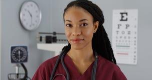 Docteur réussi de femme de couleur souriant à l'appareil-photo photo stock