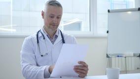 Docteur Reading Medical Papers dans la clinique images libres de droits