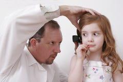 Docteur regardant dans l'oreille de petite fille Photos stock