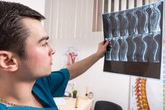 Docteur regardant l'image de rayon X montrant l'épine photos stock