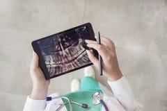 Docteur regardant le rayon X de dents sur le comprimé numérique images libres de droits