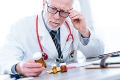 Docteur regardant une bouteille de pilules image stock