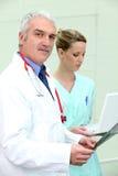 Docteur resté avec la jeune infirmière féminine photographie stock