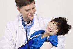 Docteur retenant un petit garçon handicapé Photo stock