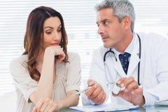 Docteur sérieux écoutant son patient Image libre de droits