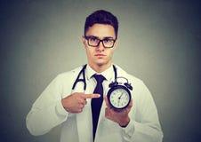 Docteur sérieux se dirigeant à l'horloge photos stock