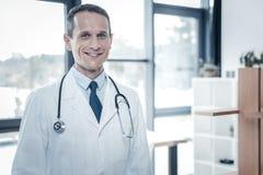 Docteur sûr qualifié se sentant bien lui-même et sourire Photos stock
